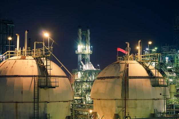 Serbatoio sfera di stoccaggio del gas nell'impianto di raffineria di petrolio e gas di notte, primo piano delle apparecchiature nell'impianto petrolchimico, illuminazione glitter di impianto industriale