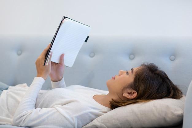 Serena ragazza rilassata sdraiata sulla schiena e leggendo il libro