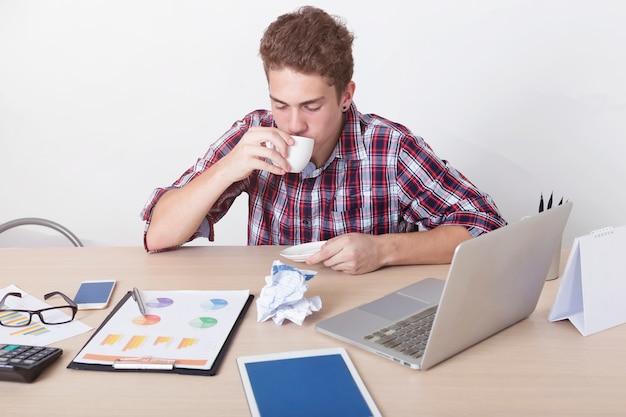 Seriamente uomo d'affari che beve un caffè nello spazio di lavoro all'ufficio. affari impegnato