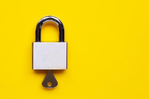 Serratura e chiave su sfondo giallo.