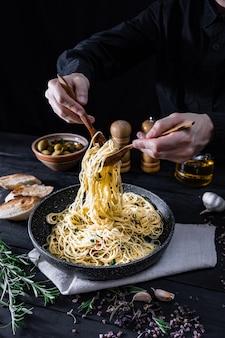 Serve pasta tradizionale italiana da una padella. mani maschii che prendono gli spaghetti in cucchiaio e forchetta, colpo in scuro