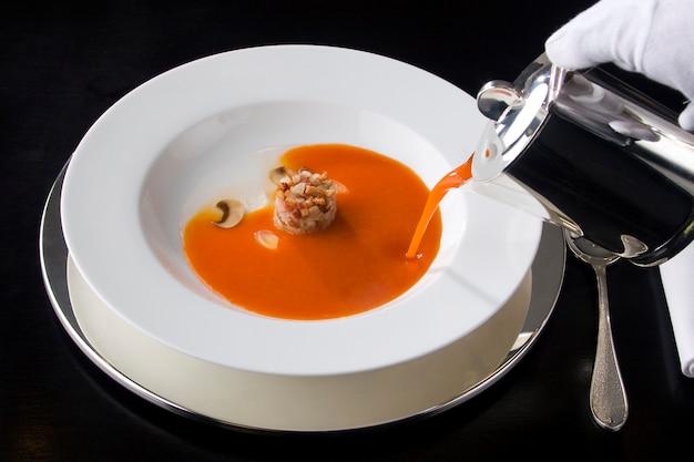 Serve zuppa di pomodoro in un ristorante gourmet.
