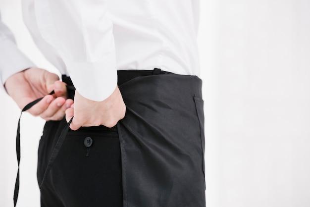 Server che lega il grembiule dietro la schiena