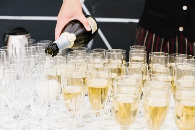 Server riempiendo bicchieri di champagne