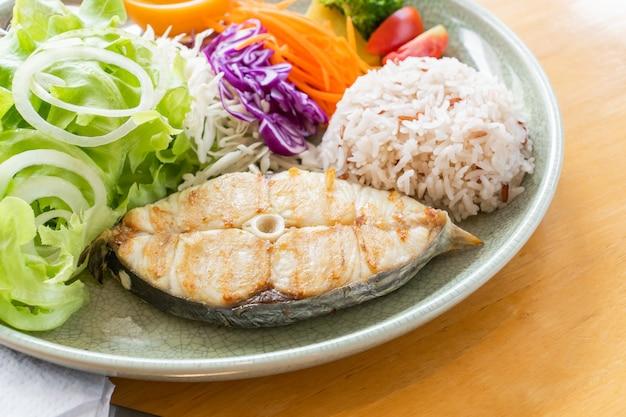 Servire insalata e pesce fritto con riso cucinato per alimenti sani.