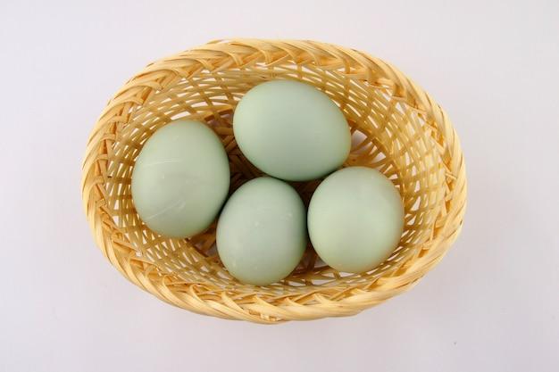 Servire le uova di anatra fresche su una superficie bianca