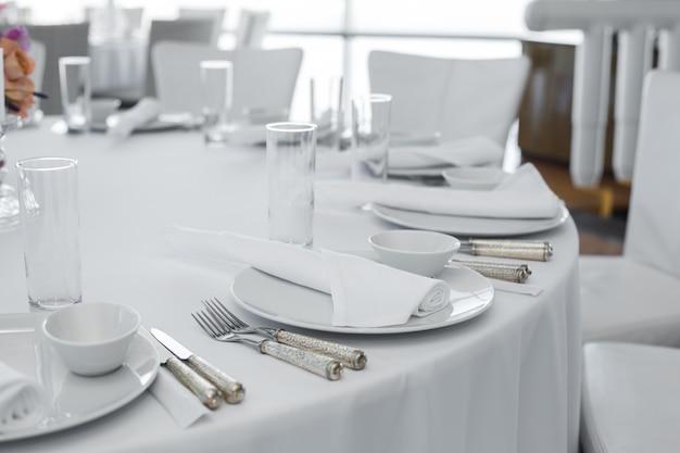 Servito al tavolo nel ristorante. layout di piatti bianchi puliti su una tovaglia bianca