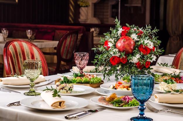Servito per il tavolo del ristorante per banchetti festivi con piatti, snack, insalate, posate, bicchieri da vino e acqua. cibo europeo in un ristorante. tavolo apparecchiato per una festa evento. ristorazione