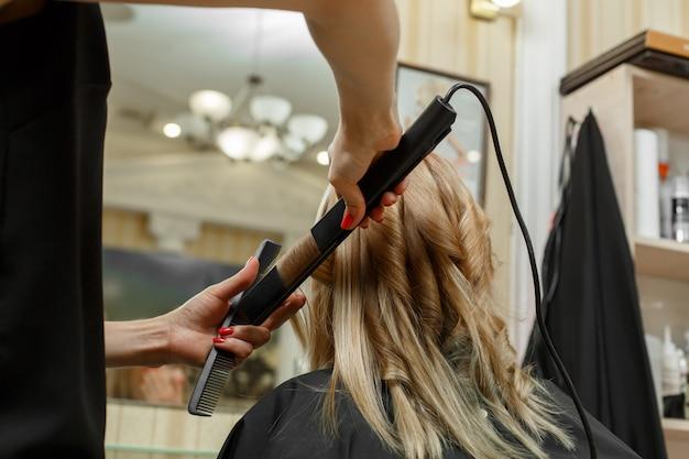 Servizi di parrucchiere. il processo di tagli di capelli per parrucchieri. processo di acconciatura. hair master con pettine e piastra per capelli. corsi di parrucchiere