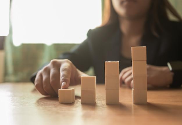 Servizio clienti e concetto di sostegno - uomo d'affari che dispone i cubi di legno con le icone di comunicazione e di contatto su loro sulla scrivania.