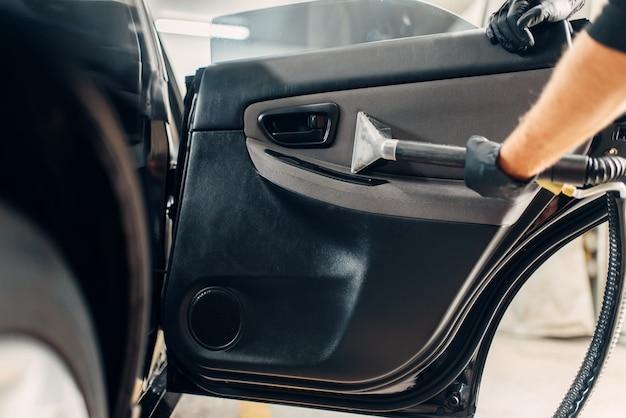 Servizio di autolavaggio, lavoratore di sesso maschile in guanti che rimuovono polvere e sporco dal rivestimento della porta.