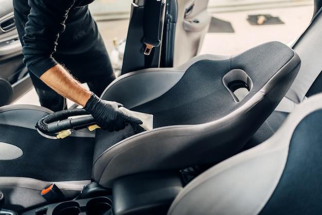 Servizio di autolavaggio, lavoratore di sesso maschile in guanti rimuove polvere e sporco.