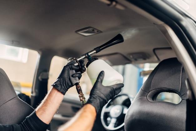 Servizio di autolavaggio, lavoratore di sesso maschile in guanti utilizzando spray speciale.