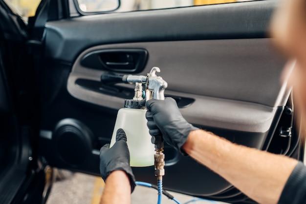 Servizio di autolavaggio, lavoratore di sesso maschile in guanti utilizzando spray