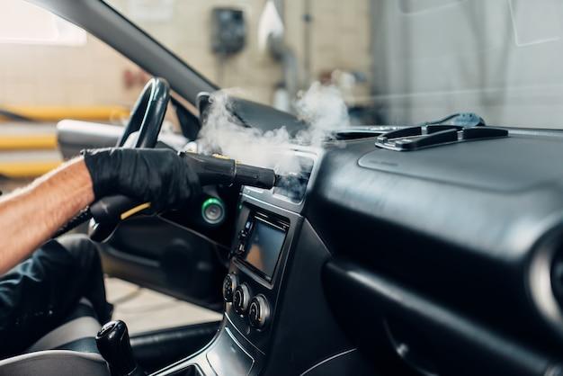 Servizio di autolavaggio, operaio maschio in guanti che rimuovono polvere e sporco con pulitore a vapore.