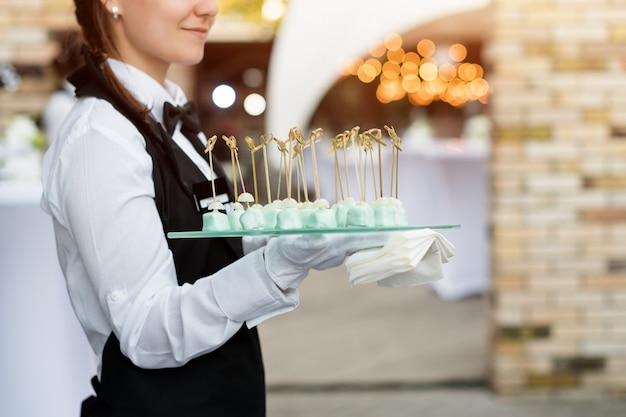 Servizio di catering. cameriere con un vassoio di antipasti. festa all'aperto con finger food, dolci.