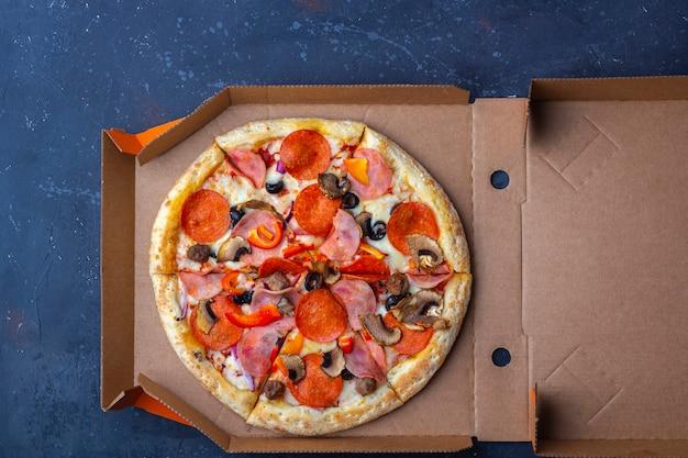 Servizio di consegna da asporto. scatola di cartone aperta con pizza fresca preparata con funghi, prosciutto e formaggio su uno sfondo scuro. concetto di fast food.