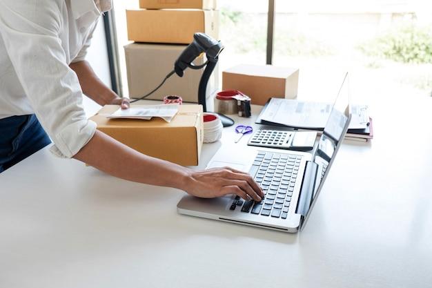 Servizio di consegna del piccolo imprenditore e scatola di imballaggio funzionante, imprenditore che controlla l'ordine