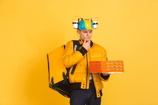 Servizio di consegna senza contatto durante la quarantena. l'uomo consegna cibo e borse della spesa durante l'isolamento. emozioni del fattorino isolate su giallo