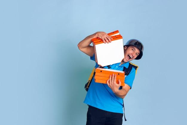Servizio di consegna senza contatto durante la quarantena. l'uomo consegna cibo e borse della spesa durante l'isolamento. emozioni del fattorino isolate sul blu