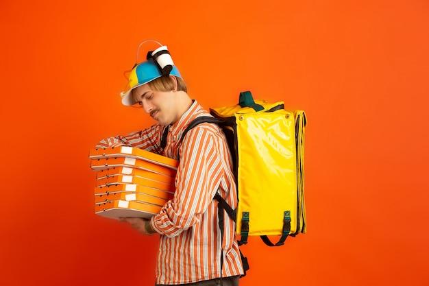 Servizio di consegna senza contatto durante la quarantena. l'uomo consegna cibo e borse della spesa durante l'isolamento. emozioni del fattorino isolato sull'arancia