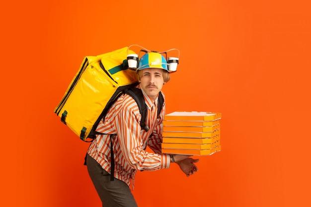Servizio di consegna senza contatto durante la quarantena. l'uomo consegna cibo e borse della spesa durante l'isolamento. emozioni di fattorino isolato su sfondo arancione.