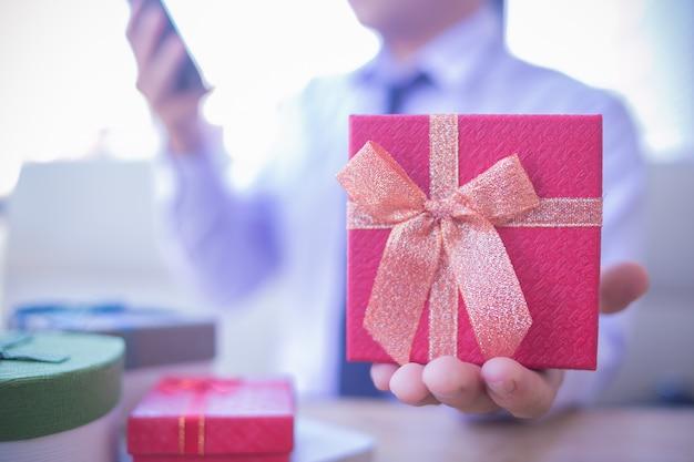 Servizio di consegna ufficio. colpo potato dell'uomo di affari in camicia che si siede allo scrittorio con il contenitore di regalo rosso.