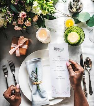 Servizio di impostazione del tavolo da pranzo elegante per la reception con la scheda del menu