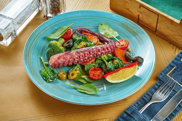 Servizio di insalata appetitosa con tentacolo di polpo e verdure al vapore su un piatto blu su un tavolo di legno. tavolo da ristorante