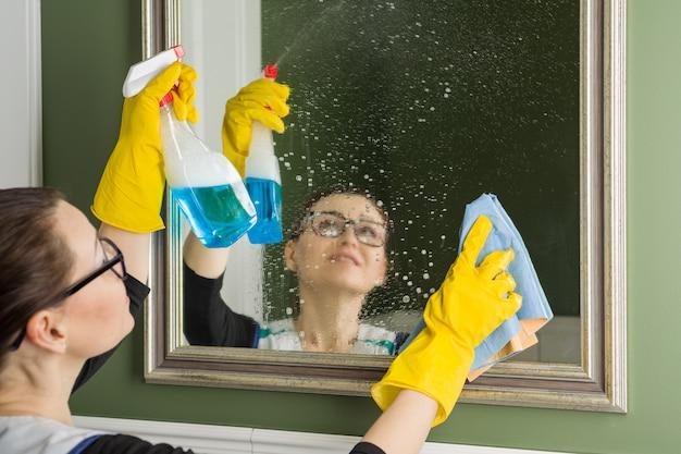 Servizio di pulizia. la donna pulisce lo specchio a casa.