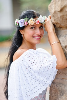 Servizio fotografico di matrimonio. ritratto di una sposa affascinante in una corona sulla sua testa. la donna sorride. girato sullo sfondo di un vecchio edificio. foto di matrimonio in stile rustico o boho.