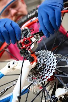 Servizio maschio della bicicletta dell'uomo di riparazione in protettivo blu
