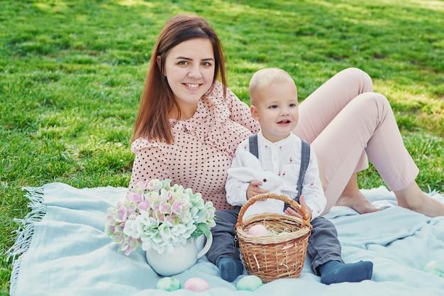 Sessione di foto di famiglia di mamma e figlio per la pasqua nel parco, accanto a loro c'è un cestino con le uova e un coniglio di pasqua