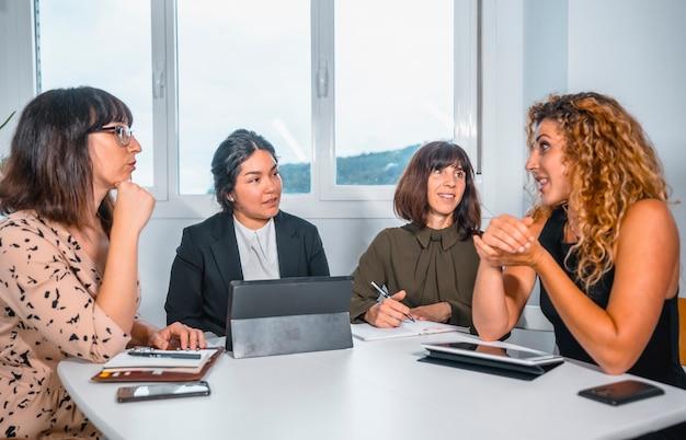 Sessione giovani imprenditori in ufficio, giovane di etnia latina e tre giovani donne caucasiche al tavolo