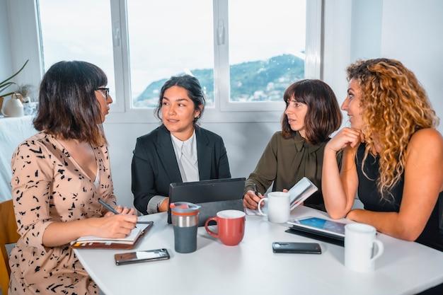 Sessione giovani imprenditori in ufficio, un giovane di etnia latina e tre giovani donne caucasiche sedute a un tavolo