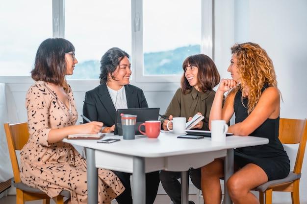 Sessione giovani imprenditori in ufficio, un giovane di etnia latina e tre giovani donne caucasiche seduti a un tavolo in ufficio una mattina d'estate