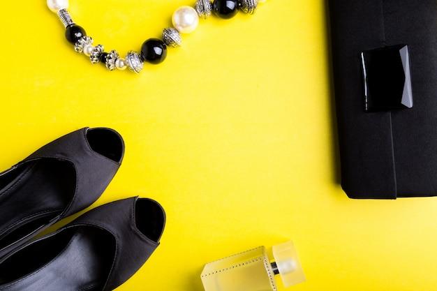 Set accessori moda donna scarpe minimal nero e giallo nero, bracciale, profumo e borsa su superficie gialla posa piatta