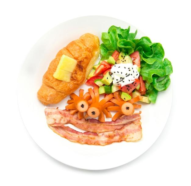 Set colazione con croissant e salsiccia di maiale, pancetta e insalata di avocado mescolano verdure in cima allo yogurt greco cospargere il sasemi nero e il cibo di quercia verde foglia per la vista quotidiana della mattina