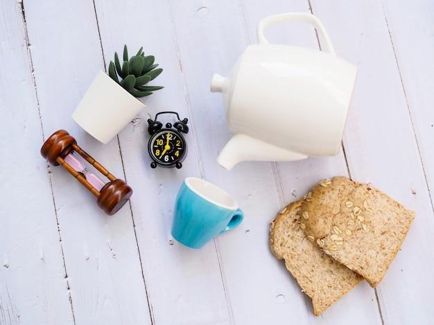 Set colazione con tazza di caffè in ceramica, teiera, sveglia, pane integrale e pianta d'appartamento di cactus.