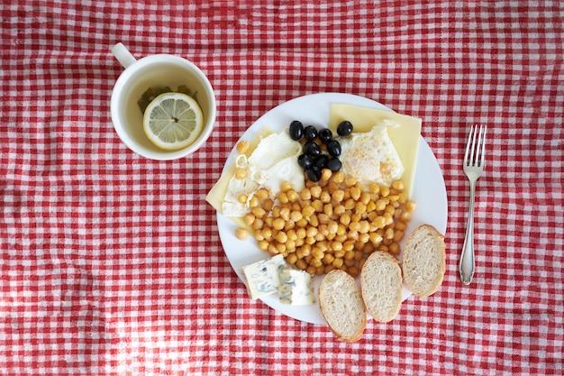 Set colazione di egss fritti con lenticchie, olive, gorgonzola e tè verde al limone, vista dall'alto su un lenzuolo rosso e bianco cheeckered