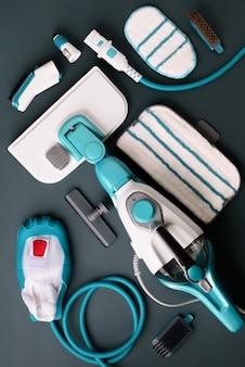 Set con moderni pulitori a vapore professionali su sfondo grigio.