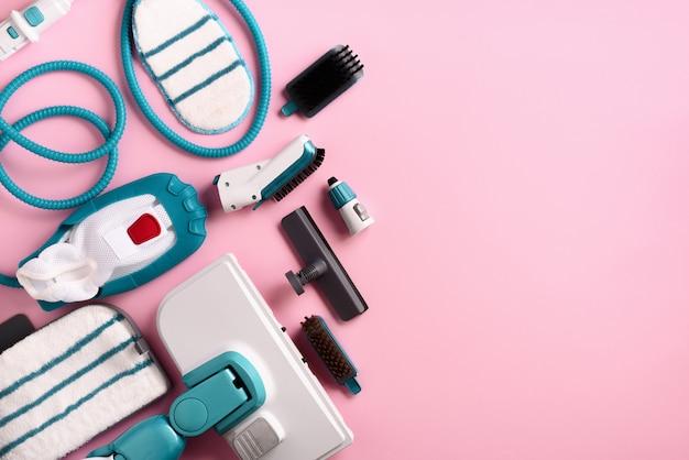 Set con moderni pulitori a vapore professionali su sfondo rosa.