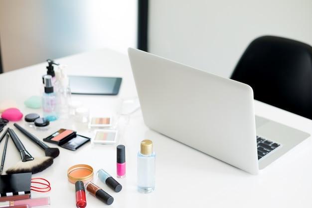 Set cosmetici sul tavolo di vestito chiaro.
