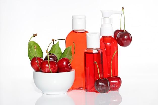 Set cosmetico per lavaggio con estratto di ciliegia in tubi di plastica e ciliegie fresche. cosmetici naturali biologici