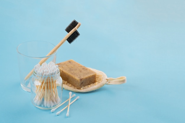 Set da bagno - spugna luffa, orecchie di bastoncini di bambù sulla superficie blu. concetto meno spreco