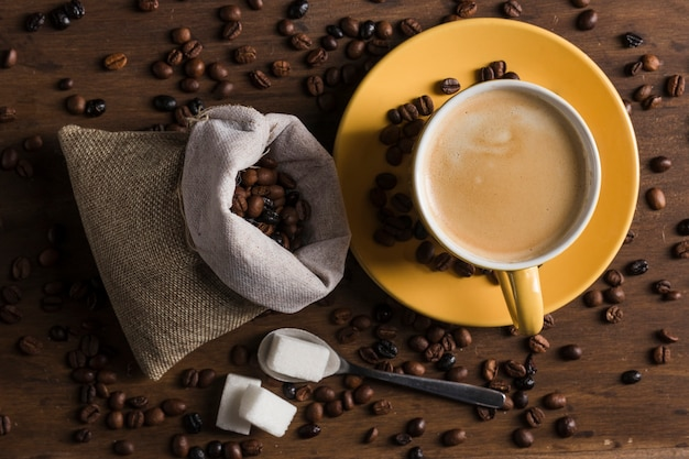 Set da caffè e zucchero sul cucchiaio vicino sacco di chicchi di caffè