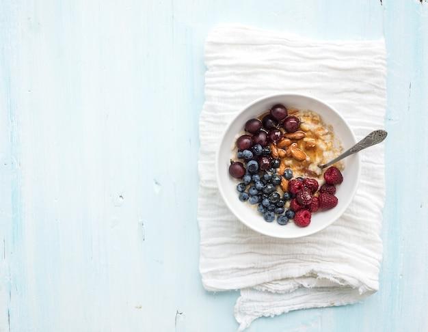 Set da colazione salutare. ciotola di porridge di avena con bacche fresche, mandorle e miele su sfondo bianco tovagliolo