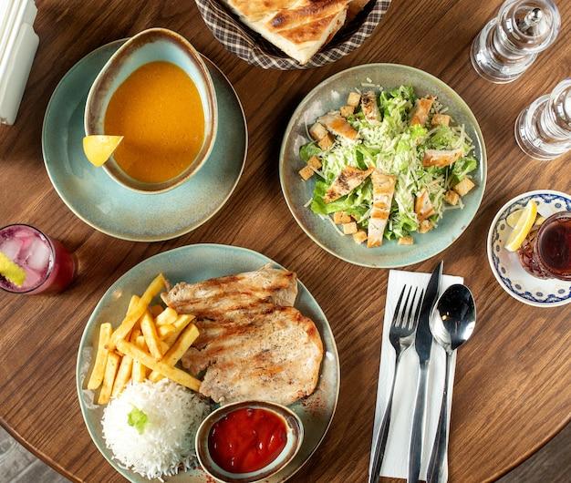 Set da pranzo con insalata caesar, zuppa di lenticchie e bistecca di pollo con riso e patatine fritte