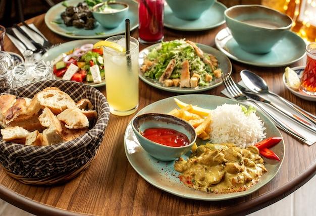 Set da pranzo con pollo servito con riso e patatine fritte cesare e insalate di verdure e limonata