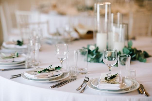 Set da tavola per la cena di nozze. elegante arredamento bianco con vegetazione